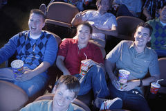 Male Friends Watching Movie In Theater. Group of multiethnic male friends watching movie in theater stock photo