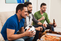 Male friends watching a soccer game. Profile view of a group of three male friends watching a soccer game on TV while drinking beer and eating pizza Royalty Free Stock Photos