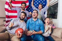 Male friends watching tv and cheering sport games on sofa at home. royalty free stock photos