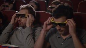 Male friends wearing 3d glasses in cinema. Spectators get ready watch 3d movie