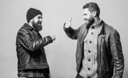 Male friendship concept. Brutal bearded men wear leather jackets. Real men and brotherhood. Friends glad see each other. Friendly relations. Friendship of royalty free stock image