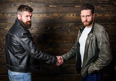 Male friendship concept. Brutal bearded men wear leather jackets shaking hands. Real men and brotherhood. Strong. Handshake. Friendship of brutal guys. Mafia stock photography