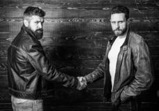 Male friendship concept. Brutal bearded men wear leather jackets shaking hands. Real men and brotherhood. Strong. Handshake. Friendship of brutal guys. Mafia stock photo