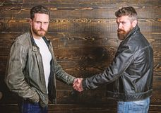 Male friendship concept. Brutal bearded men wear leather jackets shaking hands. Real men and brotherhood. Strong. Handshake. Friendship of brutal guys. Mafia royalty free stock image