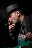 Male gambler playing poker and smokes a cigar Stock Photos