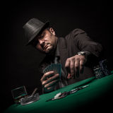 Male gambler playing poker and smokes a cigar Royalty Free Stock Image