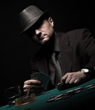 Male gambler playing poker and smokes a cigar Royalty Free Stock Photography