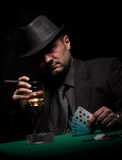 Male gambler playing poker and smokes a cigar Royalty Free Stock Images