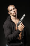 Male gangster holding a gun isolated on black Royalty Free Stock Photography