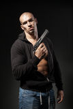 Male gangster holding a gun isolated on dark Royalty Free Stock Photo
