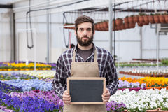 Male Garden Worker. Holding an blank chalkboard in a greenhouse Stock Photo