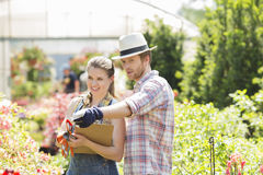 Male gardener discussing with supervisor outside greenhouse Royalty Free Stock Photo