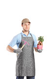 Male gardener holding a mattock and a plant Stock Images