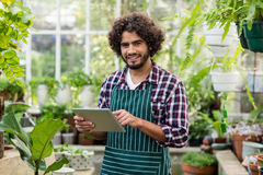Male gardener using digital tablet at greenhouse. Portrait of male gardener using digital tablet at greenhouse Stock Photo