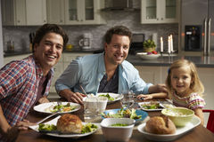 Male gay couple and daughter dining at home look to camera royalty free stock photos