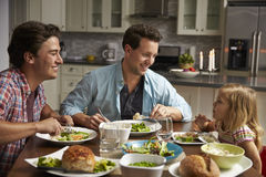 Male gay couple and daughter dining in their kitchen stock photo
