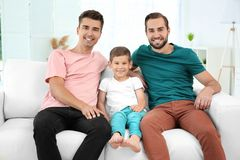 Male gay couple with foster son sitting on sofa at home. Adoption concept Royalty Free Stock Images