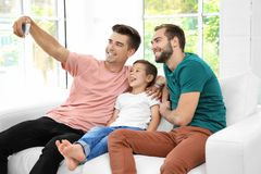 Male gay couple with foster son taking selfie. Adoption concept Stock Photography