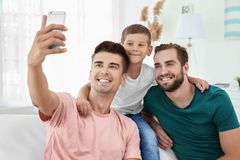 Male gay couple with foster son taking selfie. Adoption concept Royalty Free Stock Photo