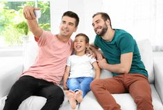 Male gay couple with foster son taking selfie. Adoption concept Stock Images