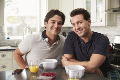 Male gay couple having breakfast in kitchen look to camera Stock Photos