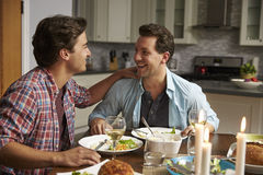 Male gay couple having a romantic dinner in their kitchen Stock Image