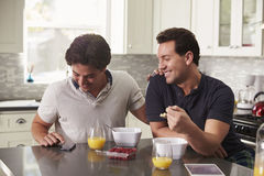 Male gay couple looking at smartphone over breakfast Royalty Free Stock Photos