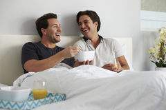 Male gay couple relax in bed eating breakfast together Stock Images