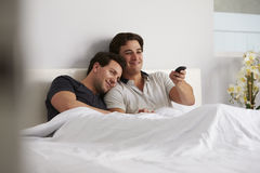 Male gay couple relax in bed together watching TV royalty free stock image