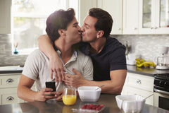 Male gay couple in their 20s kissing in their kitchen Stock Photo