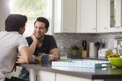 Male gay couple in their 20s talking in their kitchen Stock Photos