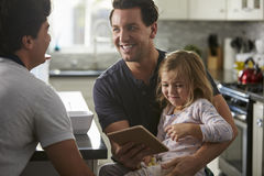 Male gay dads using tablet with daughter look at each other Stock Photography
