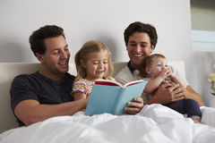 Male gay parents reading a book in bed with two kids Royalty Free Stock Images