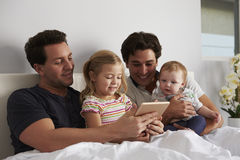 Male gay parents using tablet computer in bed with two kids Royalty Free Stock Photo