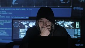 Man geek hacker in hood overworking at computer and suffers from a headache in cyber security center filled with display