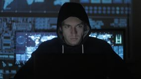 Man geek hacker in hood working at computer in cyber security center filled with display screens.