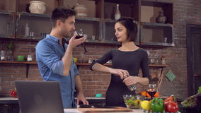 Male and girl cook healthy food with happy smile. Young woman cooking on the kitchen holding pepper mills. Near standing handsome man drinking red wine. Friends stock video footage