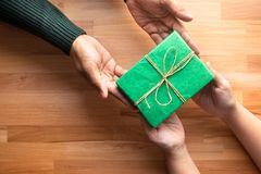 Male gives a gift present to female with wooden copy space stock photos