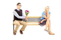 Male giving a bunch of flowers and uninterested female sitting Stock Photo