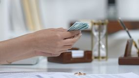 Male giving dollars to ex-wife, engagement rings on table, alimony after divorce. Stock footage stock video footage