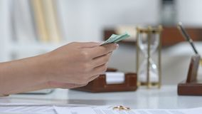 Male giving euros to ex-wife, engagement rings on table, alimony after divorce. Stock footage stock footage