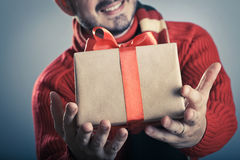 Male giving a gift box. Male giving a red ribbon gift box and smiling Royalty Free Stock Images