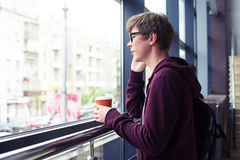 Male in glasses talking on phone and holding cup of coffee. Mid shot of male in glasses talking on phone and holding cup of coffee while leaning on handrail Stock Photography