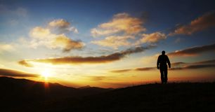 Male going on sunrise. Men silhouette on the sunset background Stock Image