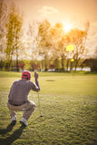 Male golf player at green. Male golf player crouching to analyze the green at beautiful sunset Royalty Free Stock Images