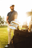 Male golf player at the green course with a club sack. Male golf player at the green sunny course with a club sack Royalty Free Stock Image