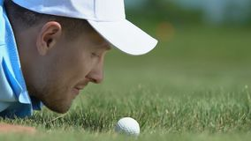 Male golf player having fun lying on grass and blowing ball into hole, close-up stock footage