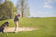 Male golf player pitching on course. Royalty Free Stock Image