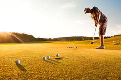 Male golf player practicing a par during sunset Royalty Free Stock Photos