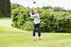 Male golf player taking a shot. Portrait of male golf player taking a shot while standing on golf course royalty free stock photos